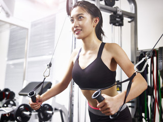 young asian woman exercising working out in gym