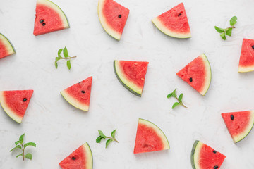 Watermelon slices, green mint leaves on white background. Top view, flat lay.