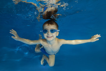 4 years boy in swimming goggles play under water in the pool