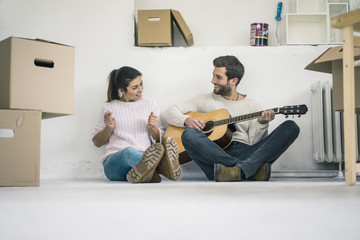 Couple sitting on the floor in new home playing guitar