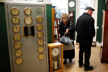 Visitors look at electric clocks at the British Horological Institute Museum in Upton