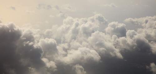 Storm clouds, colorful, heavy on blue sky background. Aerial photo from plane's window, banner