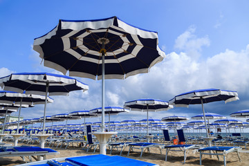 Beach umbrellas and chaise lounges. Rimini, Italy.
