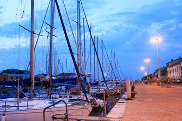 Pesaro harbour in the sunset with ancient buildings, ships, yachts. Marche, Italy