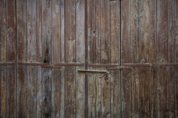 Wooden brown aged door, rusty latch and padlock. Close up, details