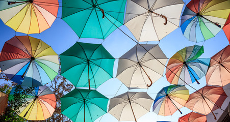 Colorful open umbrellas cover a street at Nicosia, Cyprus. Blue sky and parasols for backdrop.