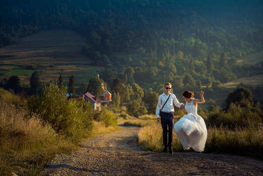 Wedding shot of the joyful attractive just married in sunglasses dancing o nthe road at the background of the mountains during the sunset.