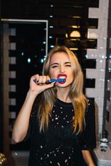 Blonde woman brushing teeth