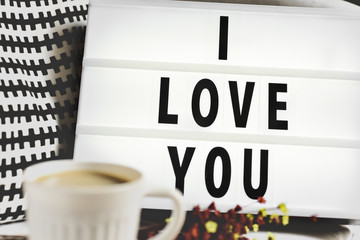 cup of coffee and text I love you in a lightbox