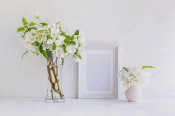 Mockup with a white frame and white spring flowers