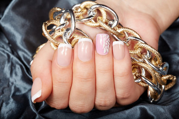 Hand with french manicured nails holding a chain necklace