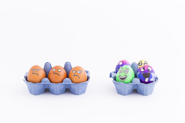 Group of colorful painted Easter eggs with funny cartoon style faces and group of grumpy looking brown eggs in light blue egg boxes on white background