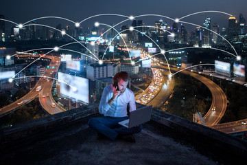 Wall Mural - young business man sitting talking mobile phone and working at night on rooftop,business business and network technology concept