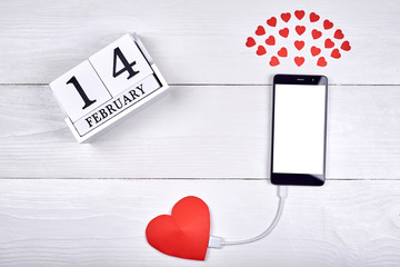 Mobile smart phone with white blank screen charging with red paper heart on white wooden background, copy space. Mockup template for Valentines Day. Love, technology concept. Top view, flat lay