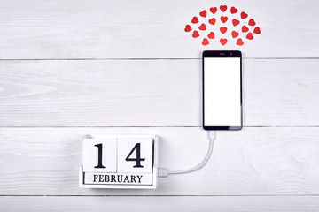 Mobile smart phone with blank screen charging with wood block calendar on white wooden background, copy space. Mockup template for Valentines Day. Love, technology concept. Top view, flat lay