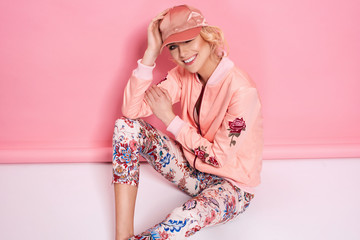 Fashion photo of a beautiful elegant young woman in a pretty bomber, pants and a cup posing over pink background. Fashion photo