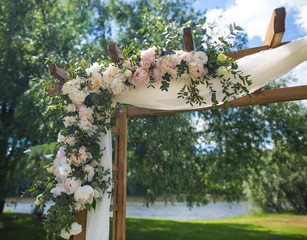 Beautiful place made with wooden square and floral decorations for outside wedding ceremony in wood. Wedding settings at scenic place. Horizontal color photography.