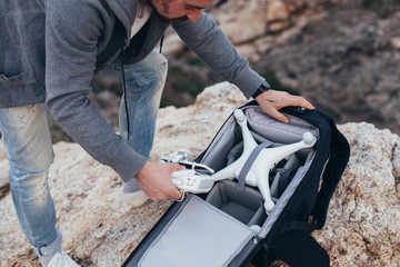 Urban adventurer or explorer, stock photographer unpacks backpack with photography equipment and drone. Ready to shoot aerial footage for sale or social media