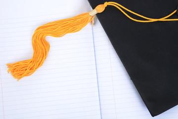 mortar board tassel notebook paper graduation concept