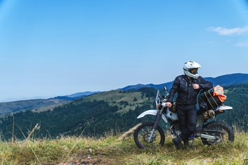 travel motorcycle off road Motorcyclist gear, A motorcycle driver looks at the mountains and coniferous forest, concept, active lifestyle,
