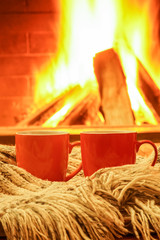 Two colorful mugs for tea or coffee; wool things near cozy fireplace.