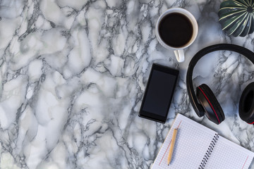 marble desk with ceramic cactus, white circular notebook, lead, coffee cup, headphones from above