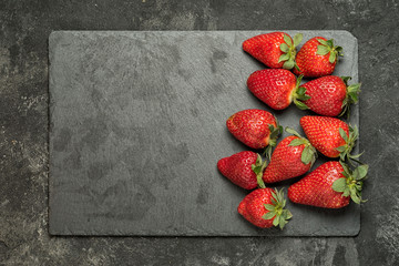 strawberry on a black stone tray laying on a black rustic cement background, top view with copy space for your text.