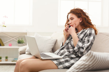 Girl with laptop and mobile sitting on beige couch.
