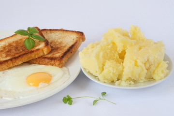 scrambled eggs with herbs and toasts on the white porcelain plate, mashed potatoes, white background