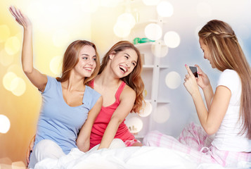 teen girls with smartphone taking picture at home