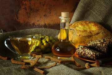 Still life with olive oil and bread in a rustic style