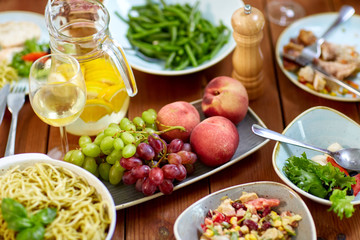 fruits, salads and pasta on wooden table