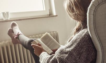 Junge Frau schaut aus dem Fenster, trinkt Tee und legt Füße zum Aufwärmen auf die Heizung