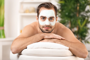 Young handsome man with cosmetic mask on face in spa salon