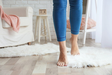 Woman walking on fluffy carpet at home