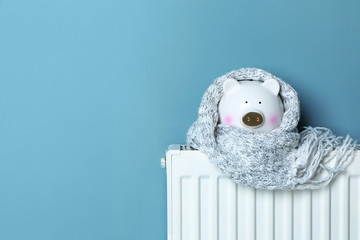 Piggy bank with warm scarf on heating radiator near color wall