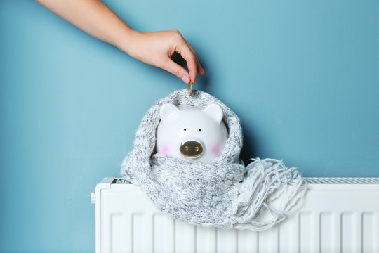 Woman putting coin into piggy bank placed on heating radiator against color background