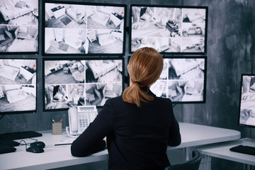 Female security guard working in surveillance room