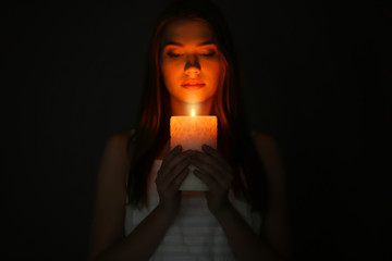 Beautiful young woman with burning candle in darkness