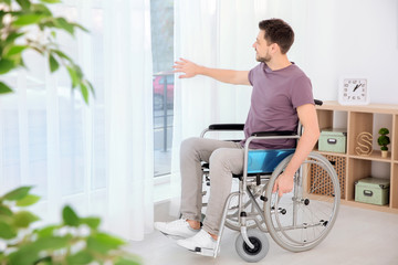 Young man in wheelchair near window indoors