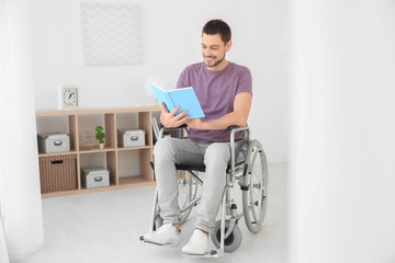 Young man in wheelchair reading book indoors