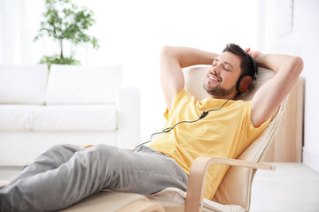 Young man listening to music while relaxing in armchair at home