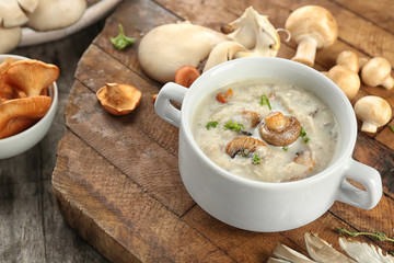 Dish with mushroom soup on wooden board