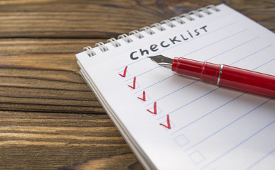 checklist, red pen on the background of a wooden table. close-up