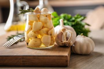 Preserved garlic in glass jar on wooden board