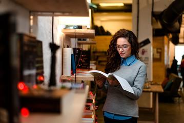 Pretty young woman choosing book to read in shelf.