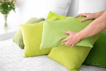 Woman putting pillow on bed, closeup
