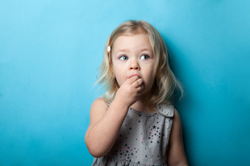 A little girl is isolated on a blue background eating a sweet candy.