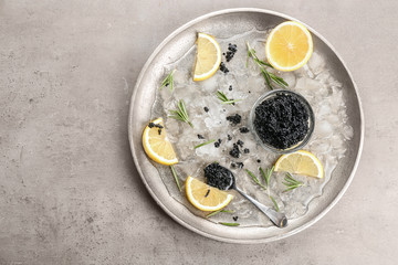 Black caviar served with ice and lemon on metal plate