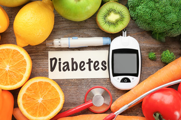 Digital glucometer, lancet pen, fruits and vegetables on wooden background. Diabetes diet